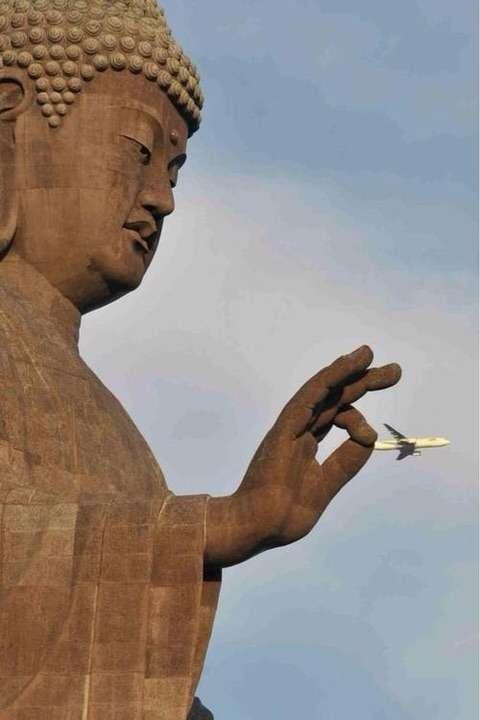 飛行機をつまんでいる牛久大仏