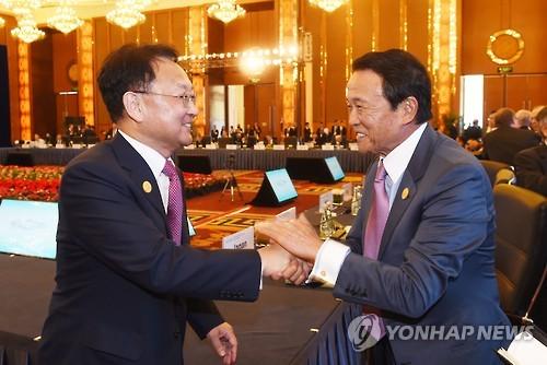 満面の笑みを浮かべ、韓国の柳一鎬(ユ・イルホ)経済副首相の手を両手で握り、日本国民の血税●兆円を差し出す麻生太郎財務大臣