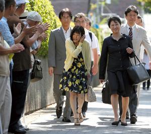支援者に出迎えられ、大阪地裁に入る青木恵子さん(中央)=10日午前9時39分、大阪市北区、上田潤撮影
