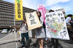 朴龍晧さんの無罪を知らせる垂れ幕と、支援者が書いた絵が掲げられた=10日午後1時34分、大阪市北区の大阪地裁、水野義則撮影