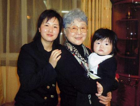 キム・ウンギョンさん(左)の娘を抱く横田早紀江さん=2014年3月、ウランバートル