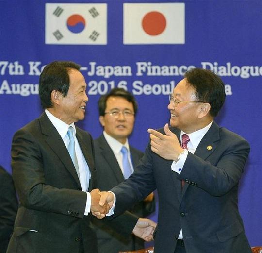 日韓財務対話を終え、笑顔で言葉を交わす麻生太郎副総理兼財務相(左)と韓国の柳一鎬・経済副首相兼企画財政相=8月27日、ソウル(共同)