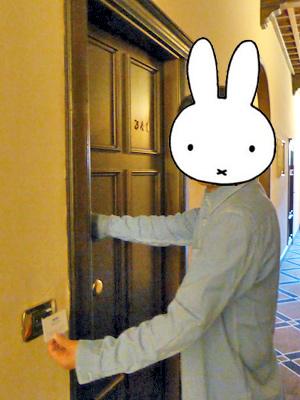 右手はドアに左手はカードキーを持って