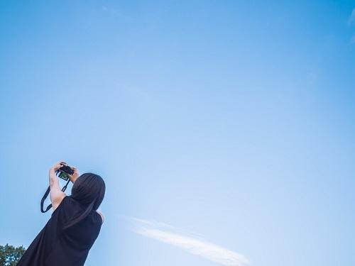青空を眺めて飛行機を探す女性
