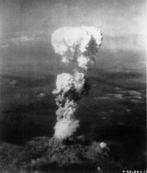 広島に投下された原爆によって巨大なキノコ雲が生じた(米軍機撮影)。キノコ雲の下に見えるのは広島市街、その左奥は広島湾。